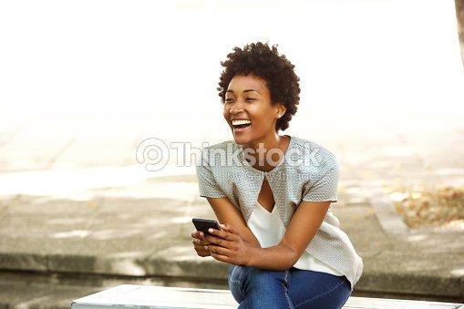 Belle jeune femme africaine souriante avec téléphone portable à l extérieur    Photo 28d539bd98c2