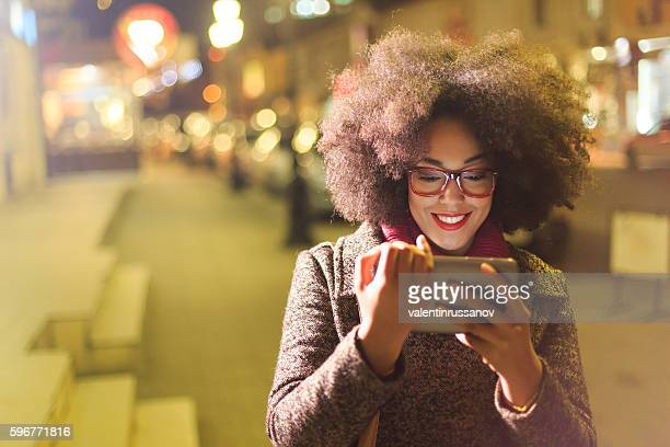 Beautiful young african woman using digital tablet at night
