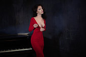 beautiful young attractive woman in sexy evening red dress with cigarette and piano. She stand near black piano Deep decollete and smoke
