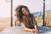 Beautiful young black woman lying down in a  wooden foot bridge at the beach