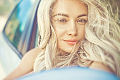 Atmospheric outdoors fashion portrait of beautiful blonde in car on the beach. Summer trip. Summer vibes