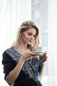 Beautiful young blonde woman in a blue robe by the window. Drinks coffee or tea from a white cup with a saucer. Morning, sunshine, bedroom window. Close-up hands and lips.