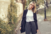 Beautiful blonde woman in urban background. Young girl wearing black blazer jacket and striped trousers standing in the street. Pretty female with straight hair hairstyle and blue eyes.