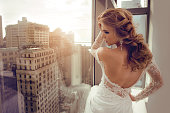 Beautiful Young bride in wedding dress posing near window
