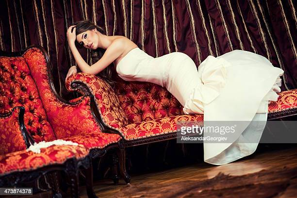 Beautiful Young Bride Lying on Sofa inside of Baroque Interior