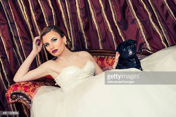 Beautiful Young Bride Lying on Sofa with Her Puppy Dog