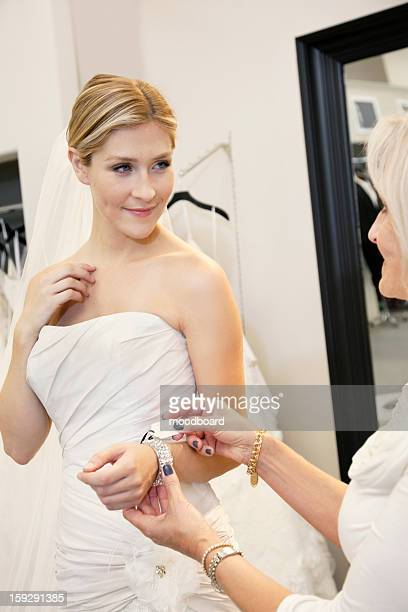 Beautiful young bride with mother looking at price tag of bracelet in bridal store
