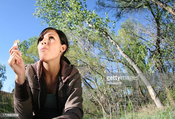 Beautiful young brunette woman eating food in the woods