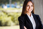 Beautiful young business woman, smiling, close up portrait. With copy space.