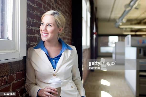 Bella giovane donna d'affari prendendo una pausa caffè in ufficio corridoio, Copyspace