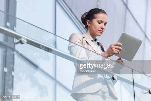 Beautiful young businesswoman using digital tablet at office railing : Foto de stock