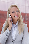 Beautiful young businesswoman using mobile phone against office building