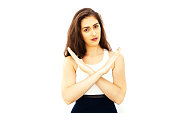 Beautiful young Caucasian woman in smart casual dress say no with crossed arms hands with copy space on isolated white background