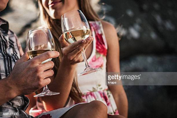 Beautiful young couple cuddling by the sea with wine