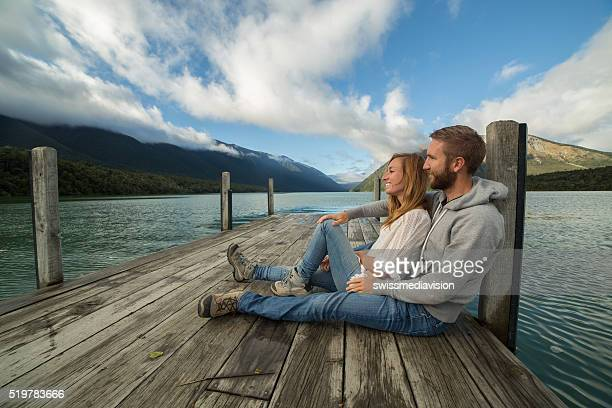 Beautiful young couple cuddling on lake pier-New Zealand
