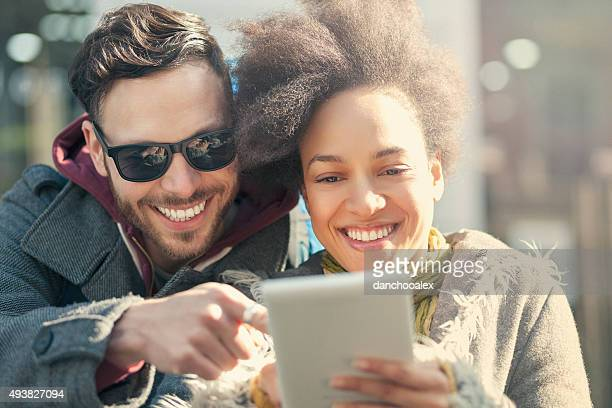 Beautiful young couple in the city using tablet PC