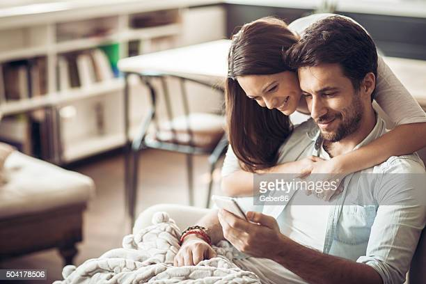 Beautiful young couple looking at smartphone