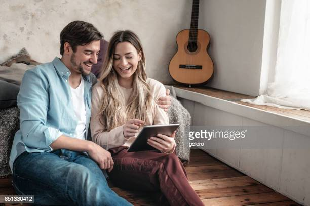 beautiful young couple looking together at digital tablet home