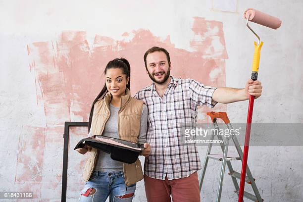 Beautiful young couple making redecoration at home