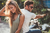 Portrait of beautiful young couple on a motorcycle. Attractive young woman with handsome young man on motorbike.