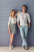 Full length portrait of beautiful young couple in casual clothes looking at camera and smiling, standing against gray wall