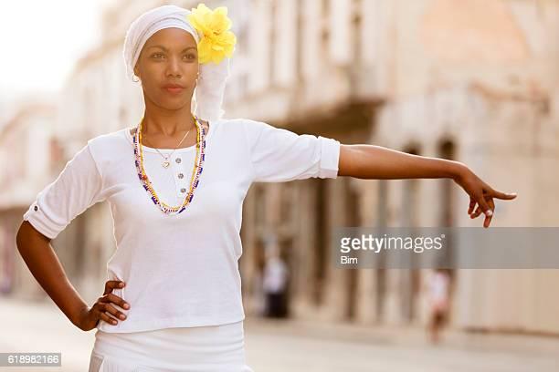 Beautiful, young Cuban woman calling taxi in Havana, Cuba