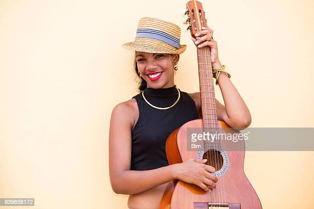 Beautiful young Cuban woman with guitar, Havana, Cuba