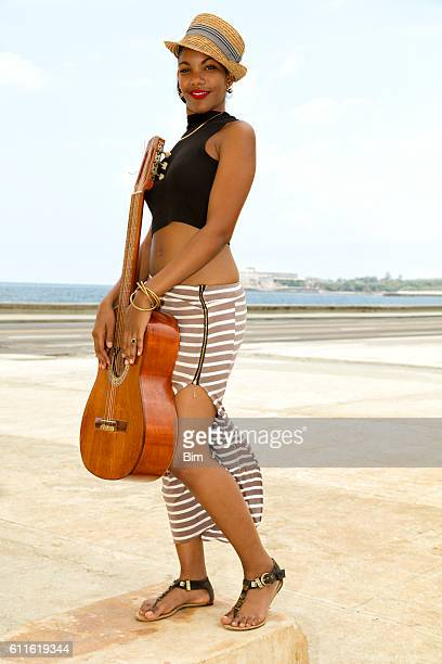 Beautiful young Cuban woman with guitar, The Malecon, Havana, Cuba