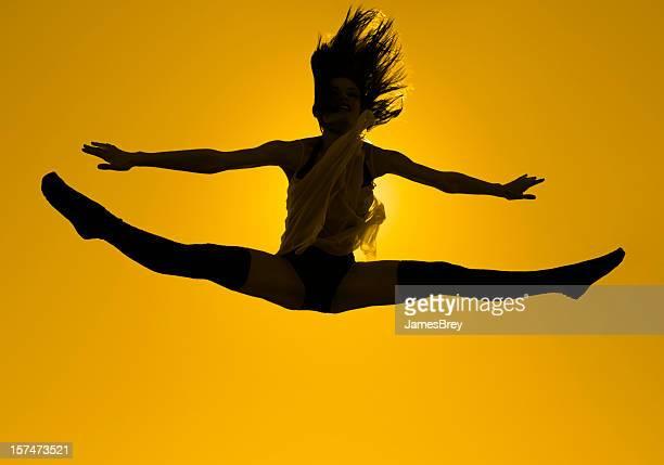 Schöne junge Tänzerin Sprünge in Splits, Hintergrundbeleuchtung von der Sonne