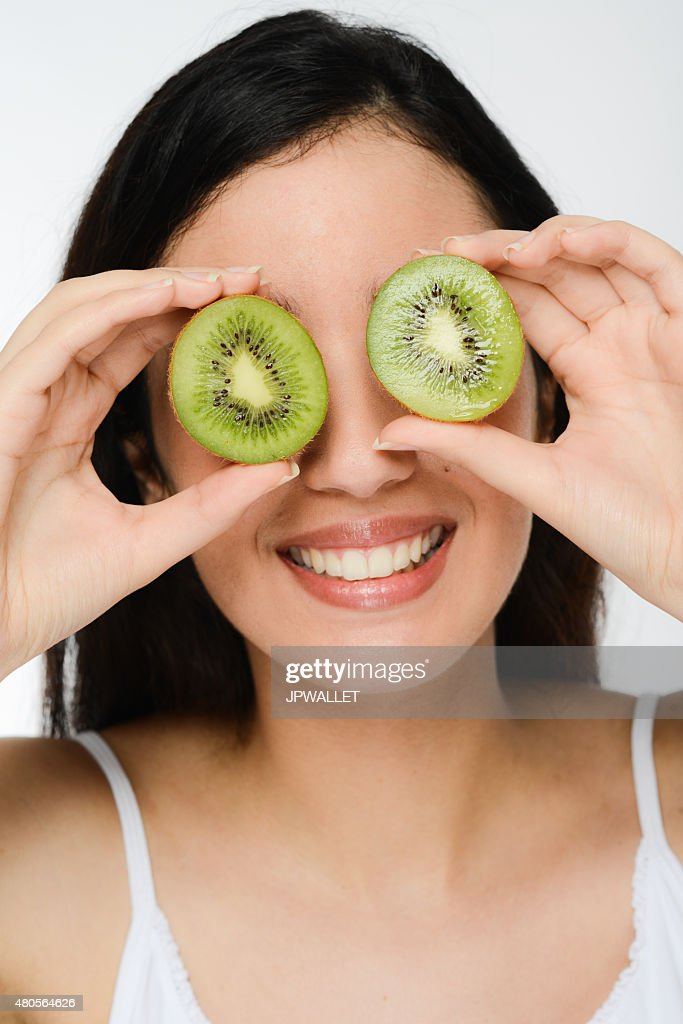 beautiful young ethnic brunette showing slices of a kiwi fruit : Stock Photo