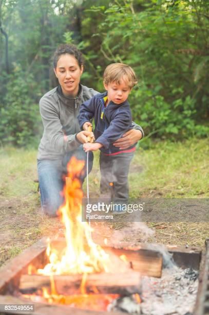 Belle jeune maman ethnique contribue à son fils rôtir un se more sur le feu de camp