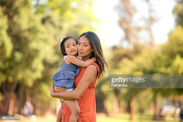 Beautiful young ethnic mother hugging her daughter