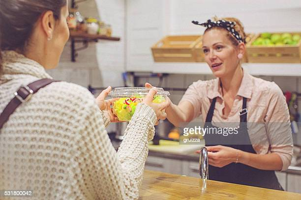 Beautiful young female small business owner serving organic cake