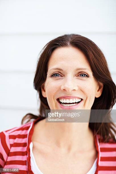 Beautiful young female smiling against a wall