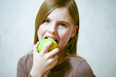 Beautiful young girl eating green Apple, light background