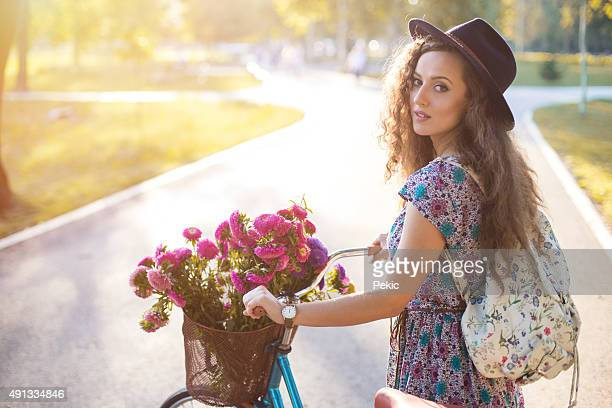 Beautiful young girl in a hat with a bicycle