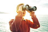 Beautiful young girl in an orange jumper looks through binoculars at the sea on a bright sunny day, low angle