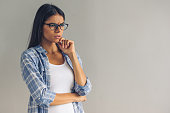 Beautiful young pensive girl in casual wear and eyeglasses is looking away and thinking, on gray background