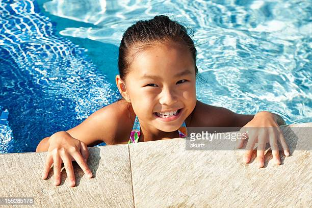 Beautiful young girl playing in the pool on Vacation
