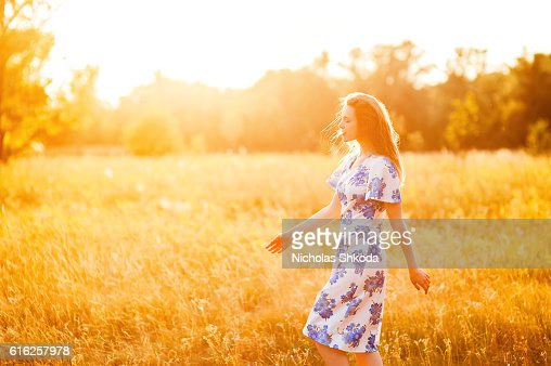 Beautiful young girl walking flower park sunset background Soft focus : Foto de stock