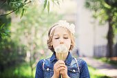 Beautiful Young Girl with Blonde Hair. Prom Hairstyle and Dandelion Flowers
