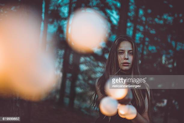 Beautiful Young Girl with Light bulbs at Night in Forest