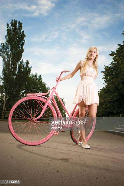 Beautiful young girl with vintage bicycle painted in pink color