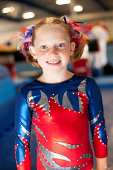 """""""Color image of a cute gymnast in gym wearing red, blue competition leotard."""""""
