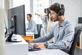 Beautiful young handsome customer support operator with hands-free set working on computer in call centre