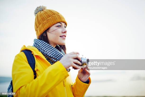 Beautiful young hiker holding vintage camera against clear sky