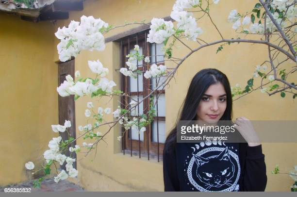 Beautiful young hispanic woman between white bougainvillea tree. flowers