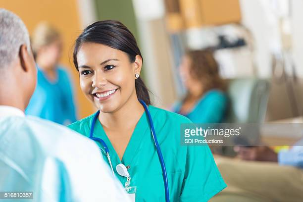 Beautiful young hospital nurse talking with senior female doctor