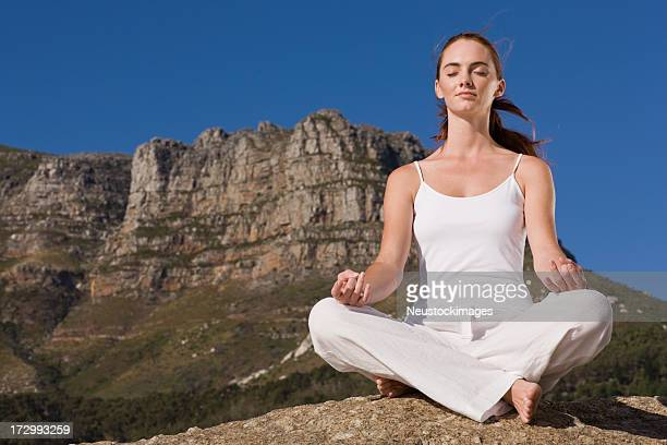 Beautiful young lady meditating on rock
