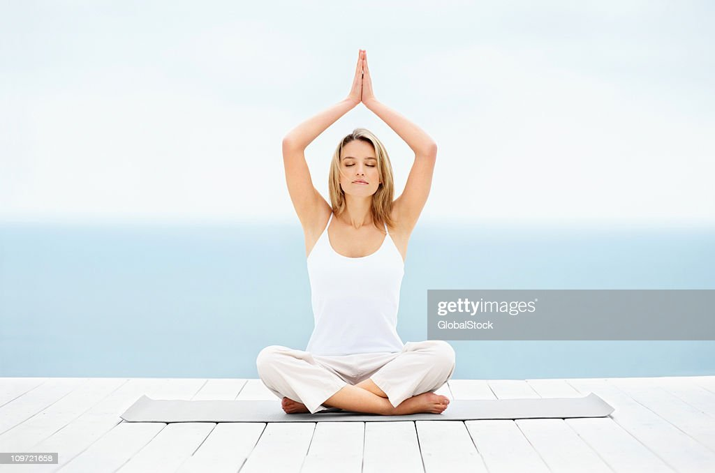 Beautiful young lady practicing yoga outdoors : Stock Photo